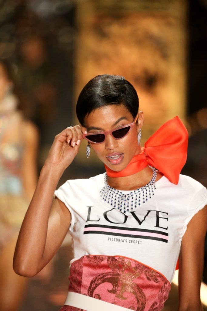 Victoria's Secret Fashion Show 2018: Jourdana Phillips with short, sleek pixie haircut, wearing micro sunglasses with slogan top on the runway