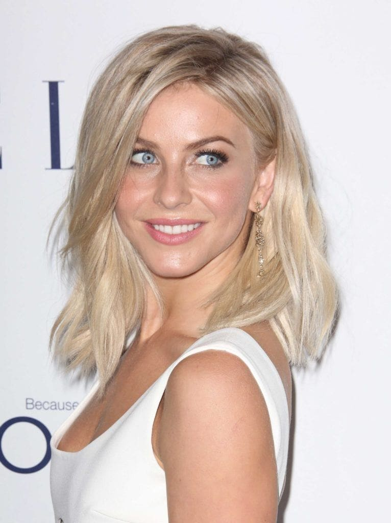Shades of blonde hair: Julianne Hough with shoulder length wavy light blonde hair wearing a white sleeveless dress
