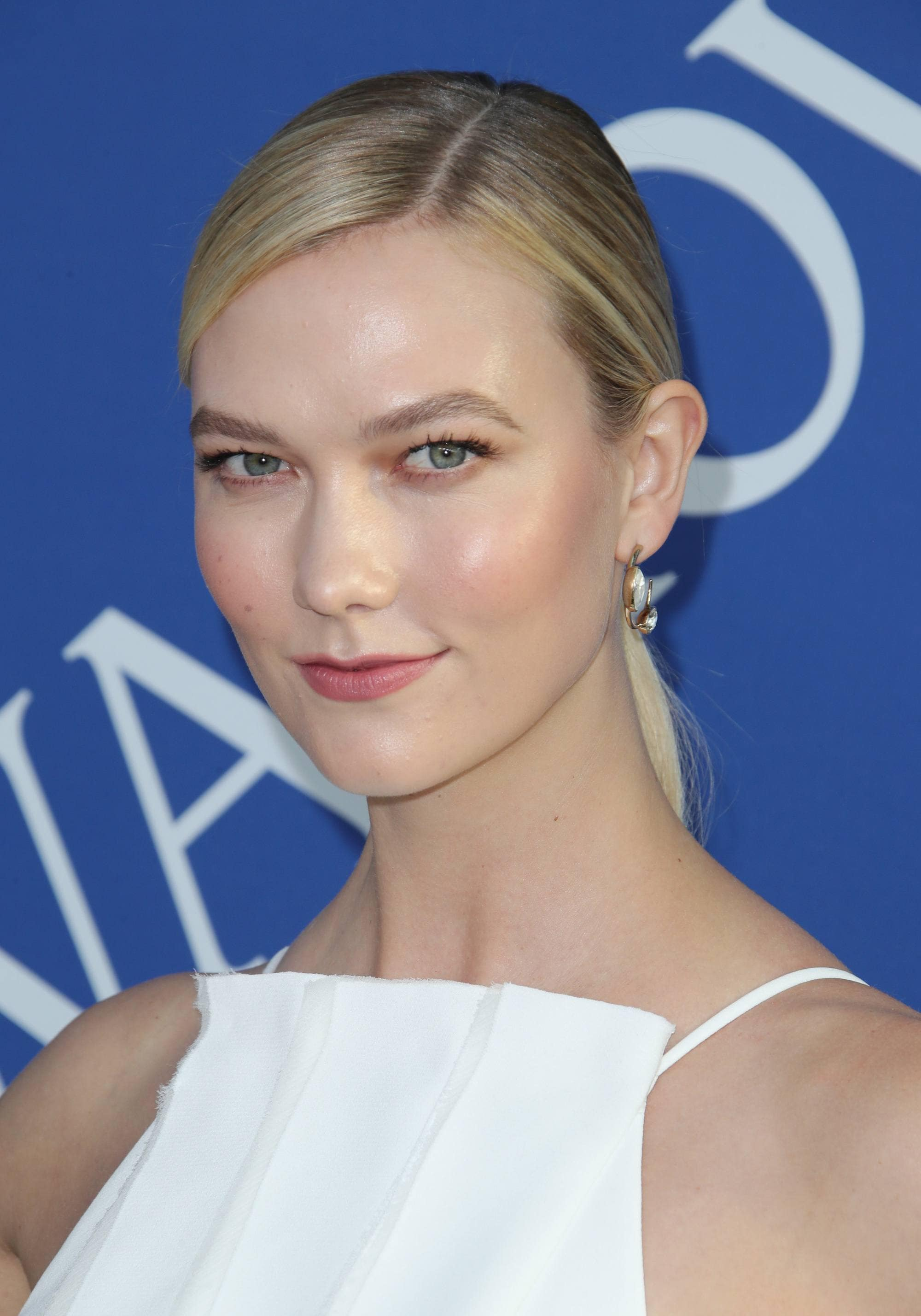 Easy hairstyles for fine hair: Karlie Kloss with straight highlighted blonde hair in side parted low ponytail.