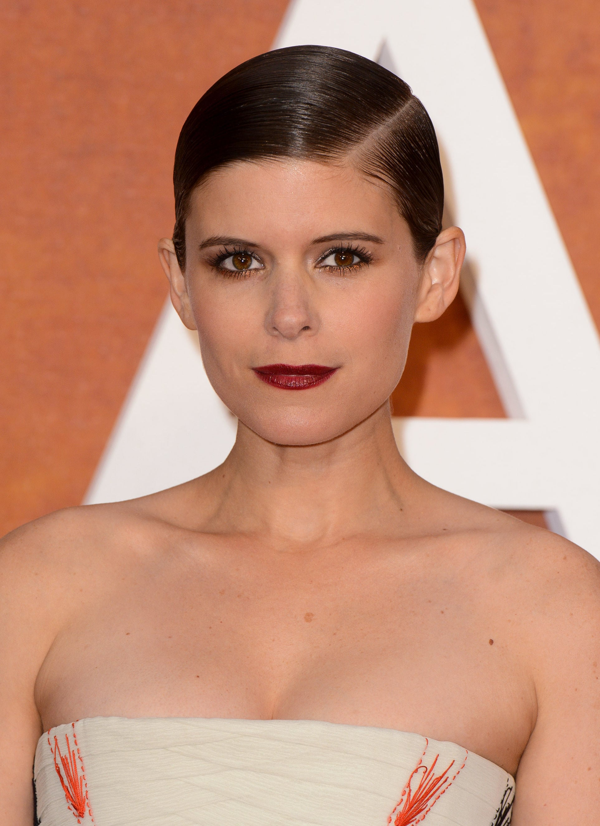 Formal hairstyles for short hair: front view of kate mara with wet look smoothed back hair in side parting