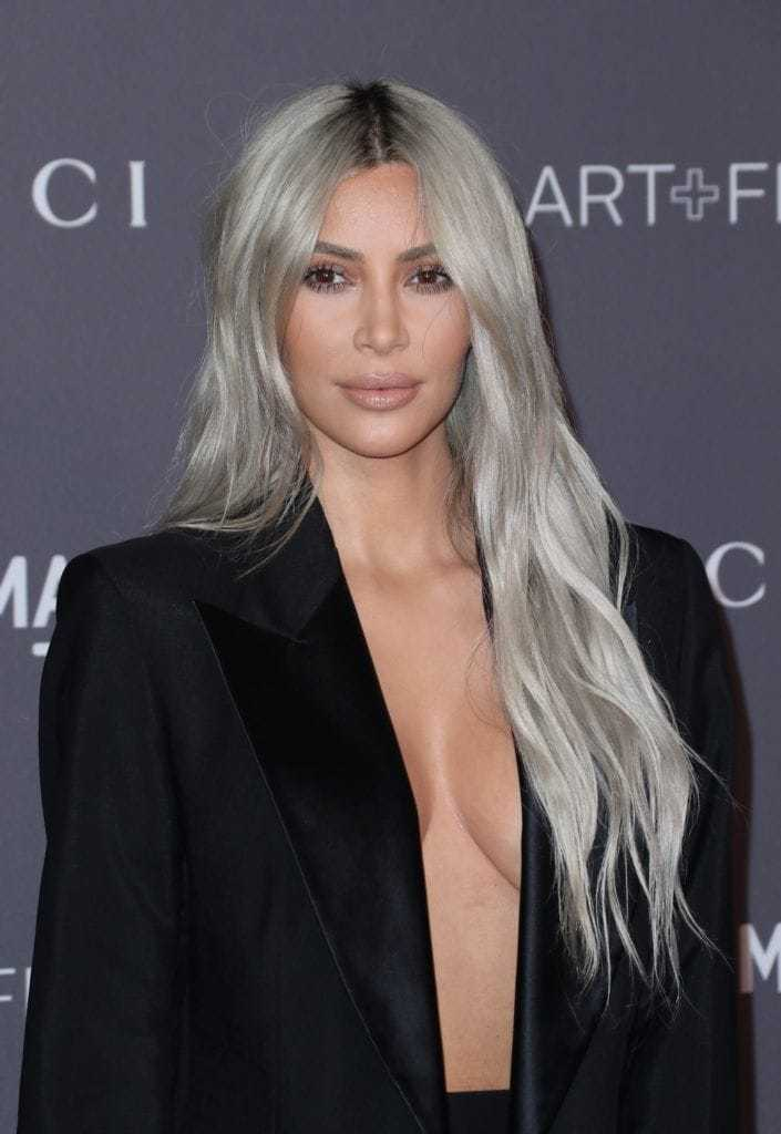 Shades of blonde hair: Kim Kardashian West with very long wavy silver blonde hair wearing a black blazer dress.