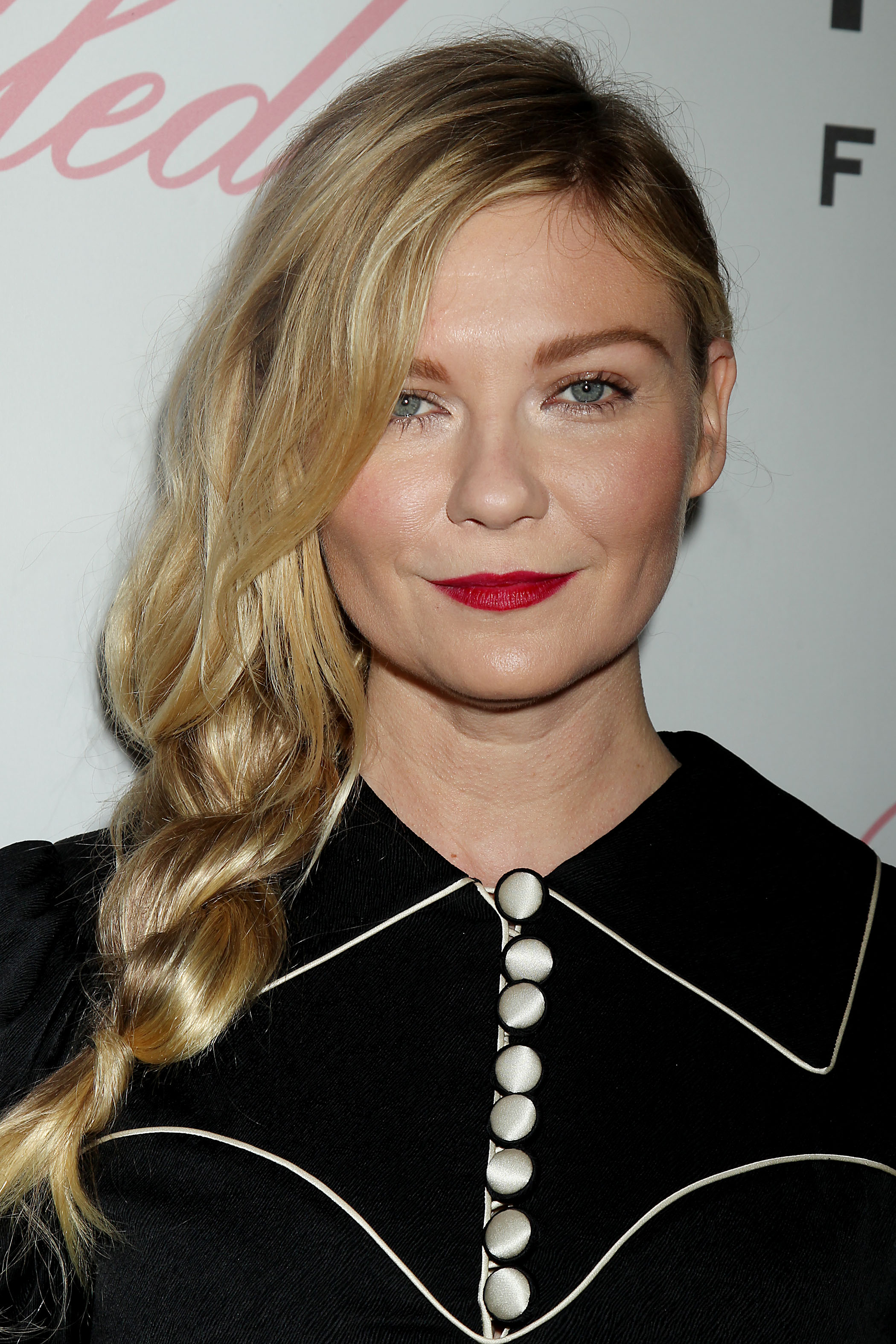 Easy hairstyles for fine hair: Kirsten Dunst with long golden blonde hair styled in a side twisted braid wearing a navy collared top.