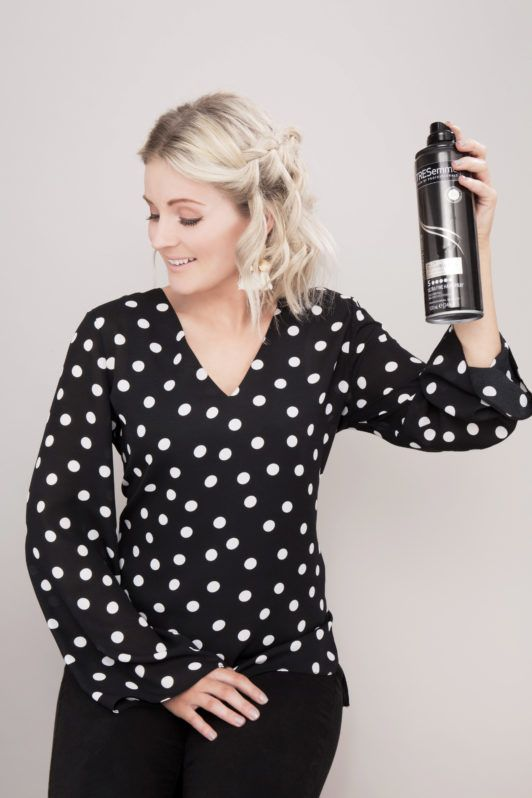 How to do a waterfall braid: Influencer Laura's Little Locket with short blonde wavy hair and waterfall braid spraying the TRESemmé Ultimate Shine Hold Hairspray