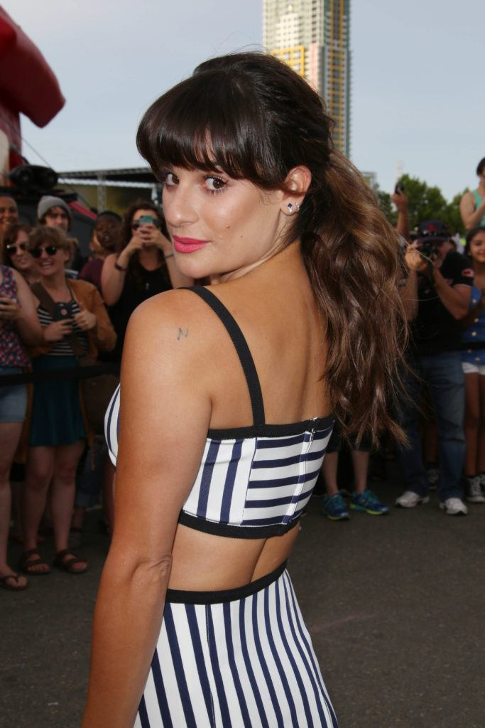 Ponytail with bangs: Lea Michele curved bangs and long brown curly ponytail.
