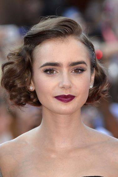 front view of lily collins with brown bob in side parting with curls