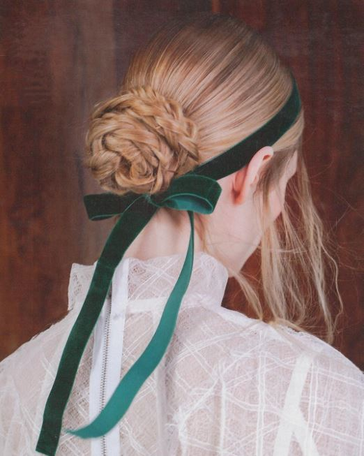back side view of blonde hair in low braided bun with emerald coloured velvet ribbon bow headband