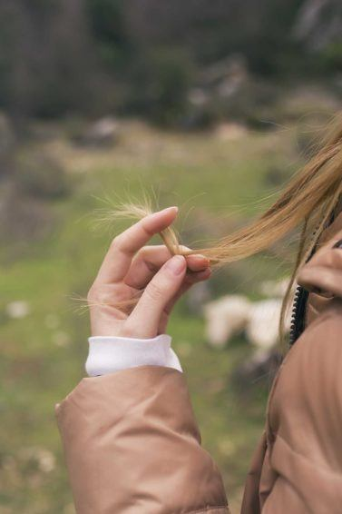 Shampoo for split ends: Back view close-up of a dark blonde haired model holding the ends of hair in her hand, standing outside in a grassy area