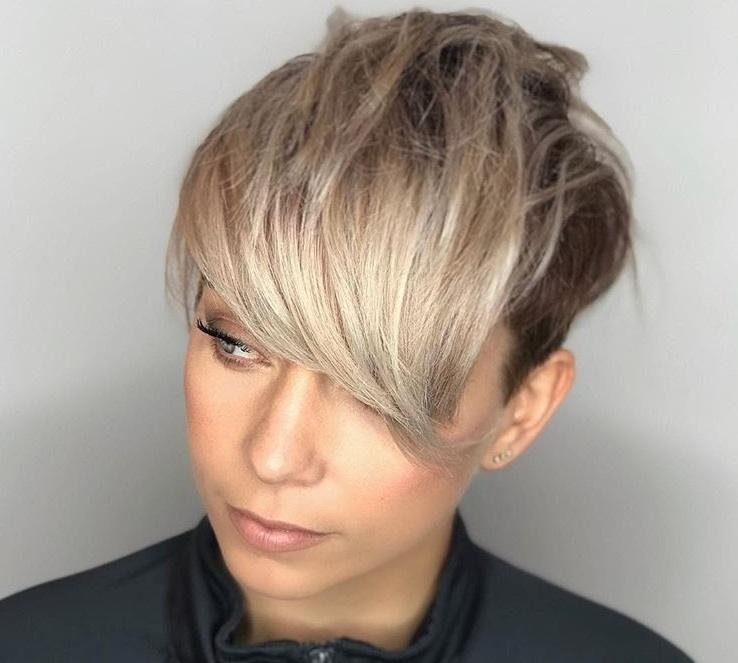 close up shot of woman with an ash blonde wavy long pixie, complete with a side-swept fringe, wearing black and posing in a salon