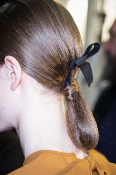 Party hairstyles for medium hair: Brown hair in low ponytail bun with a black bow in backstage image at Rochas FW17 runway show.