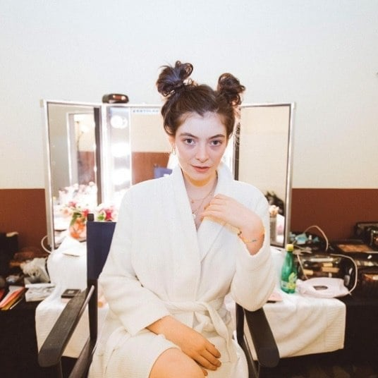 singer lorde backstage in a robe with her hair in cute space buns