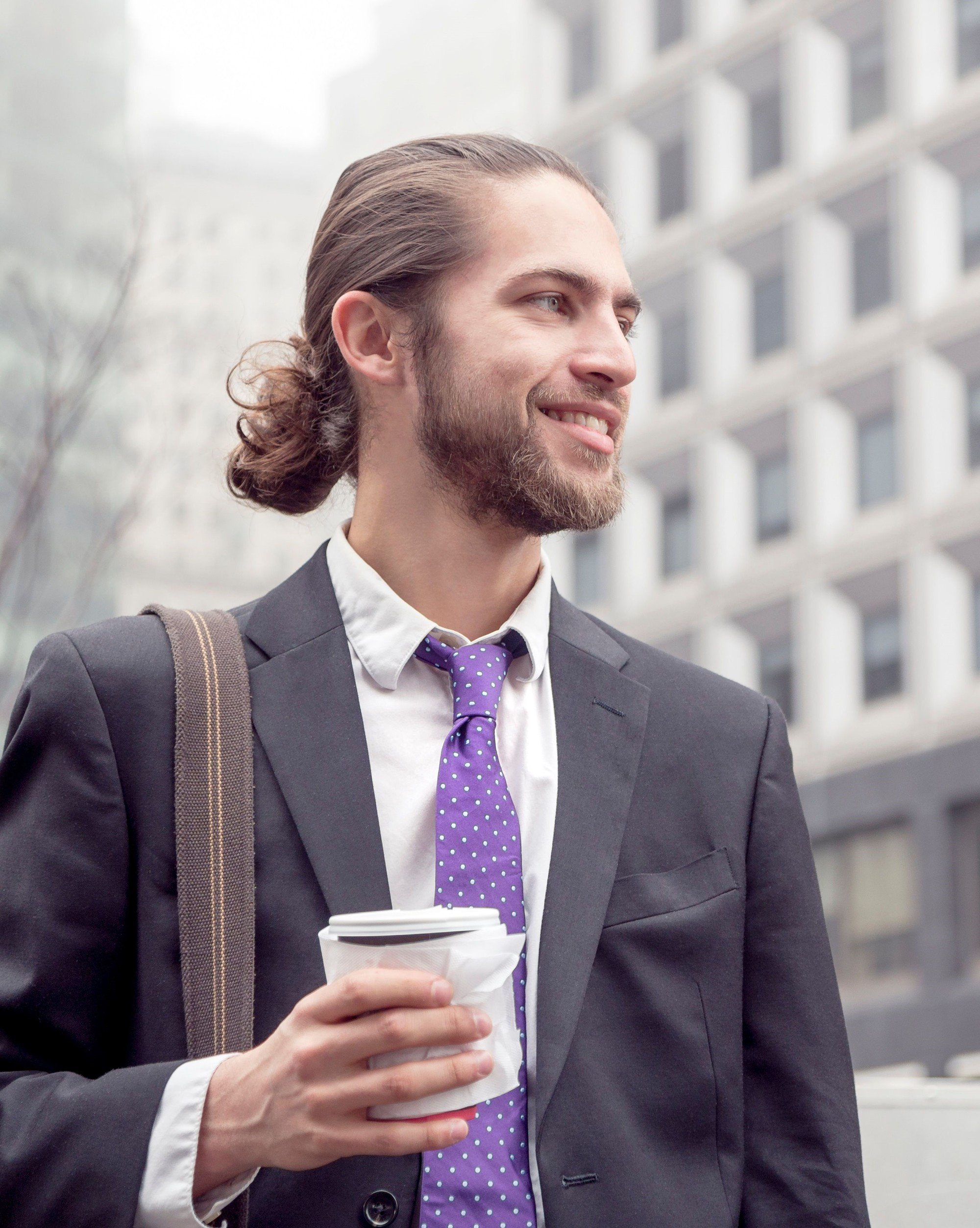 Shot of a brown haired man with a low man bun hairstyle with a beard, dressed in a suit and purple tie and holding a coffee cup