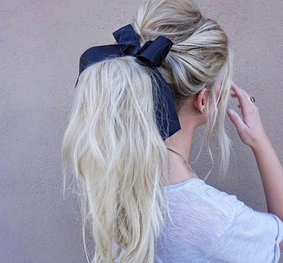 back shot of woman with ash blonde ponytail, wearing white top with hair bow in it, posing against a neutral background