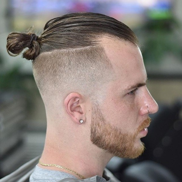 Side view of a man with brown hair styled in a man bun with a bald fade and shaped neat beard