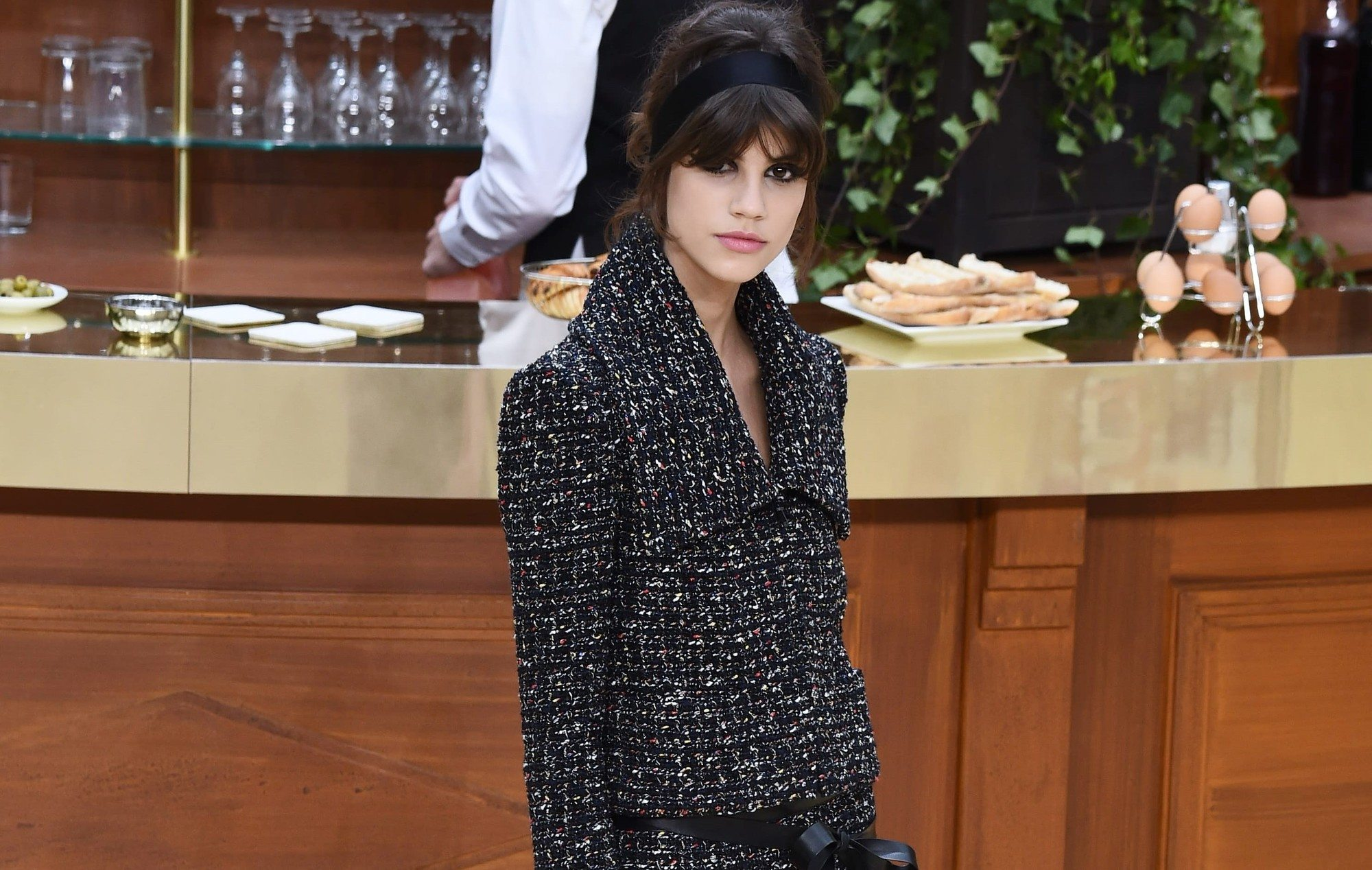 close up shot of model on the chanel runway with mini bouffant hairstyle with headband hair accessory, wearing smart suit outfit