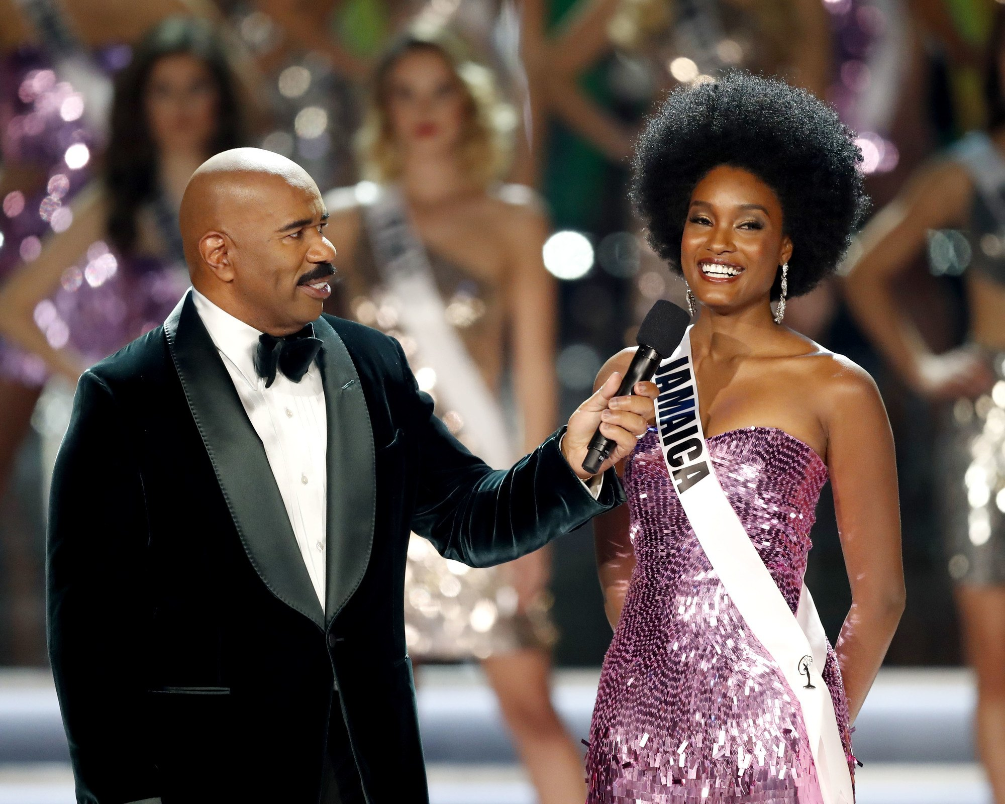 close up shot of miss jamaica's davina bennett on miss universe stage with her natural hair. wearing purple dress