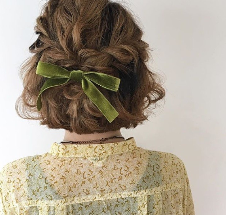 Woman with short light brown hair styled into a half-up, half-down twist that has been tied together with a green velvet hair bow, wearing green top and posing against a white background