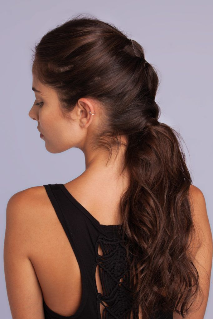 Vintage updo hairstyles: Side shot of a woman with chestnut brown hair styled into a faux hawk messy ponytail