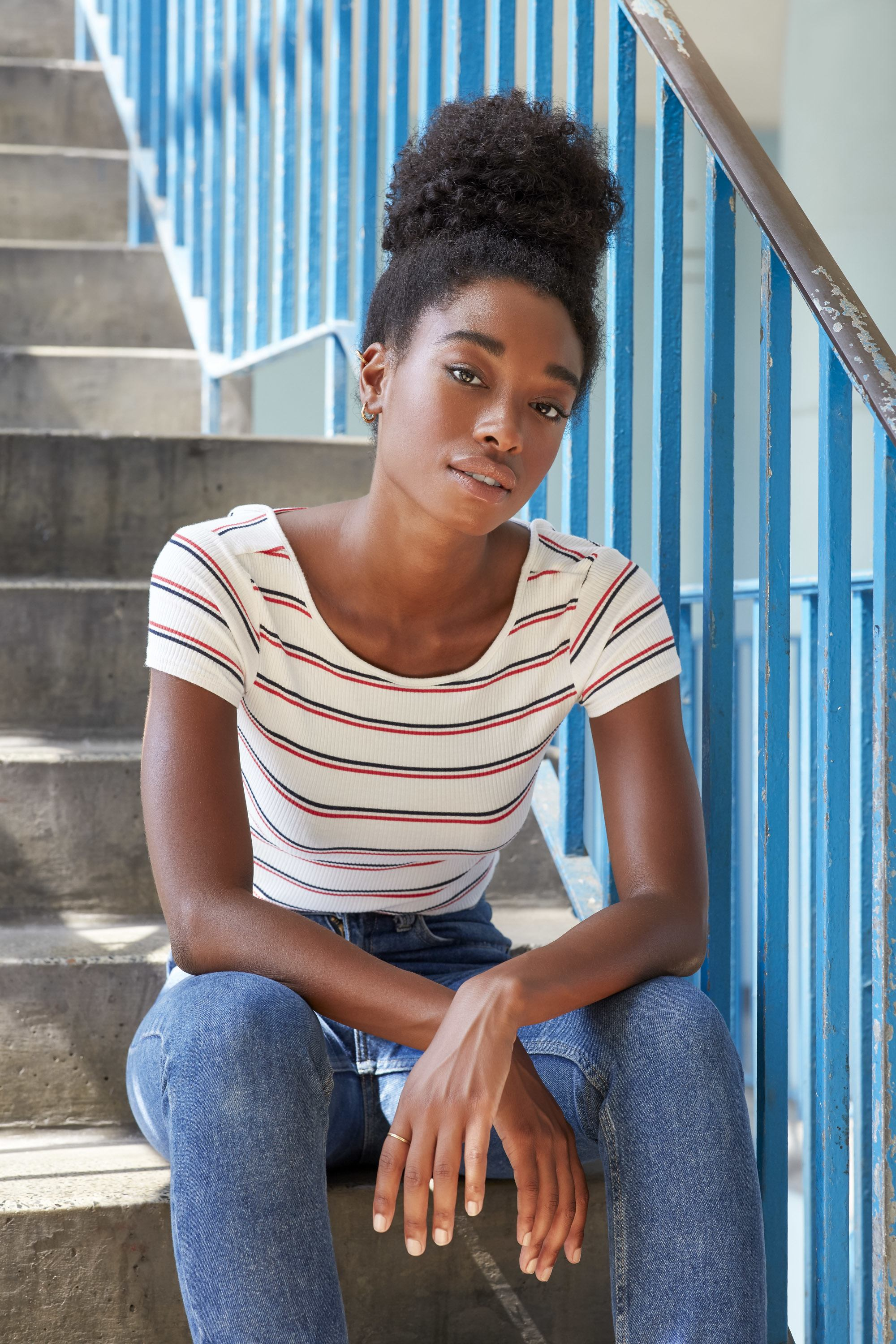 Low manipulation hairstyles: Young black woman with a high bun pineapple hairstyle sitting on stairs, wearing blue jeans and a white and red striped t-shirt