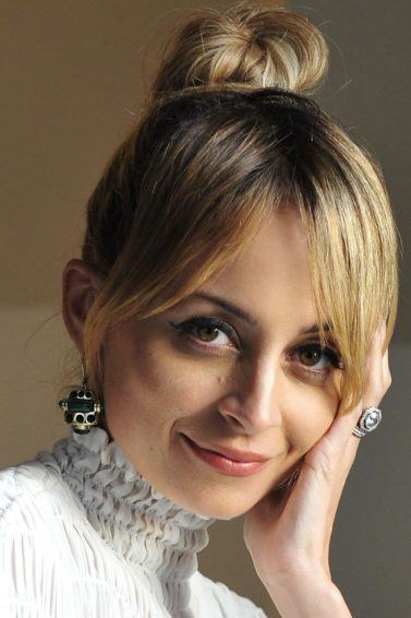 close up shot of nicole richie with blonde hair styled into a bun updo, posing and wearing white top