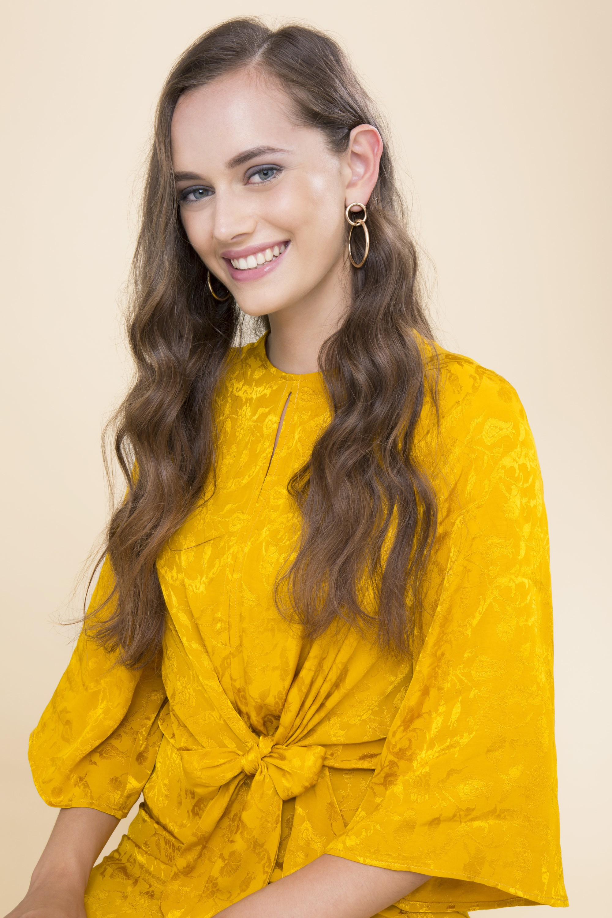 brunette woman in a yellow dress with wavy hair
