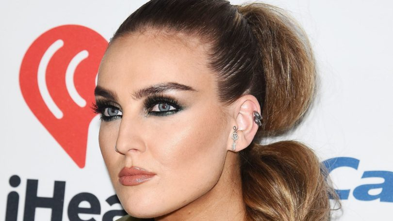 little mix singer perrie edwards in a green silky bomber jacket with her bronde hair in a side bubble ponytail
