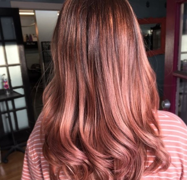 back view of a girl with shoulder length pinky rose gold hair with curled ends