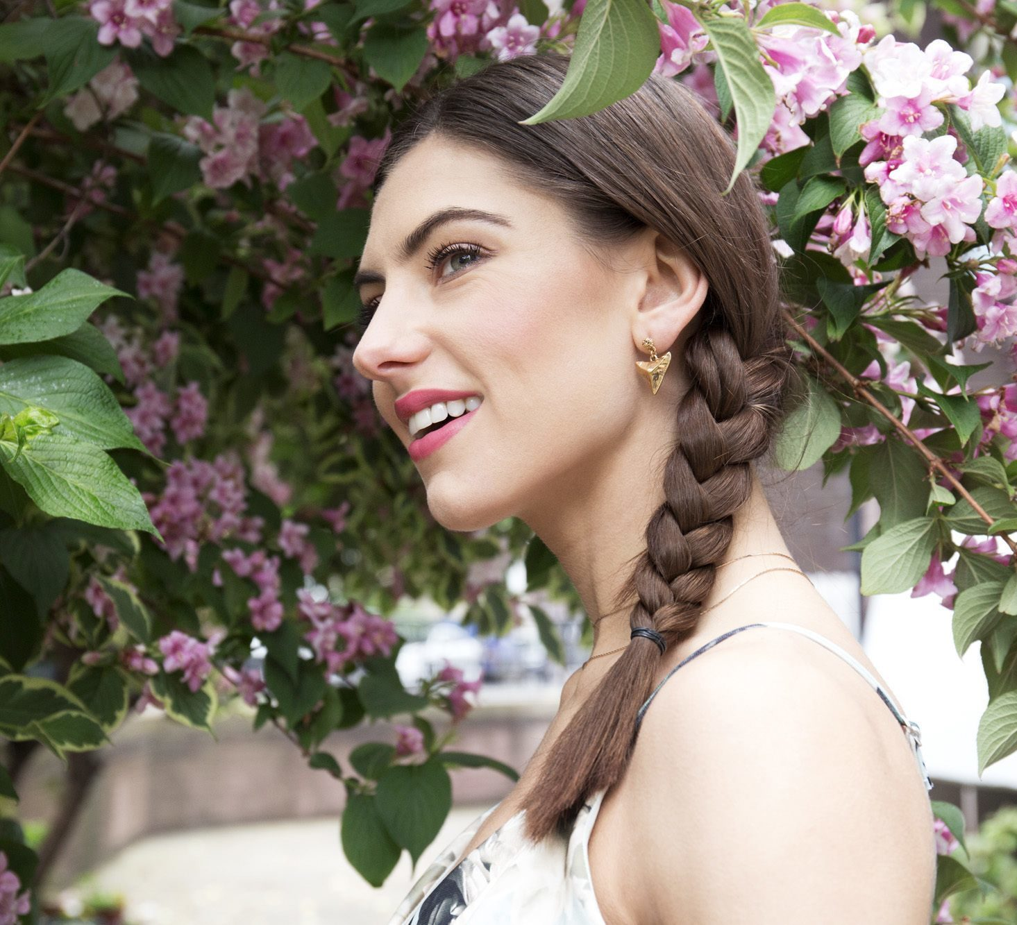 brunette woman with medium length hair styled in a side braid shot outside under trees