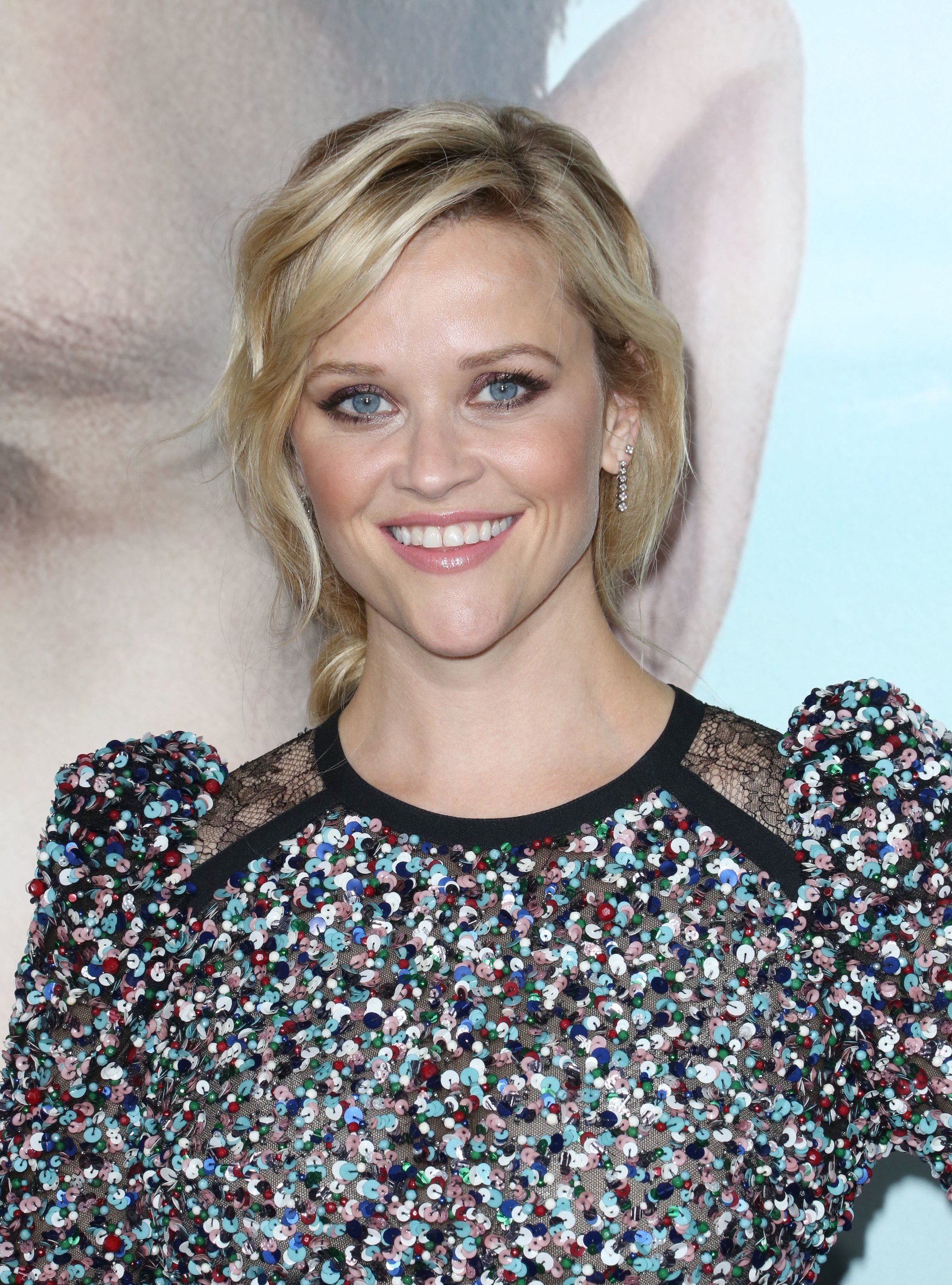 Reese Witherspoon with blonde wavy hair styled in a low ponytail with a sweeping side fringe.