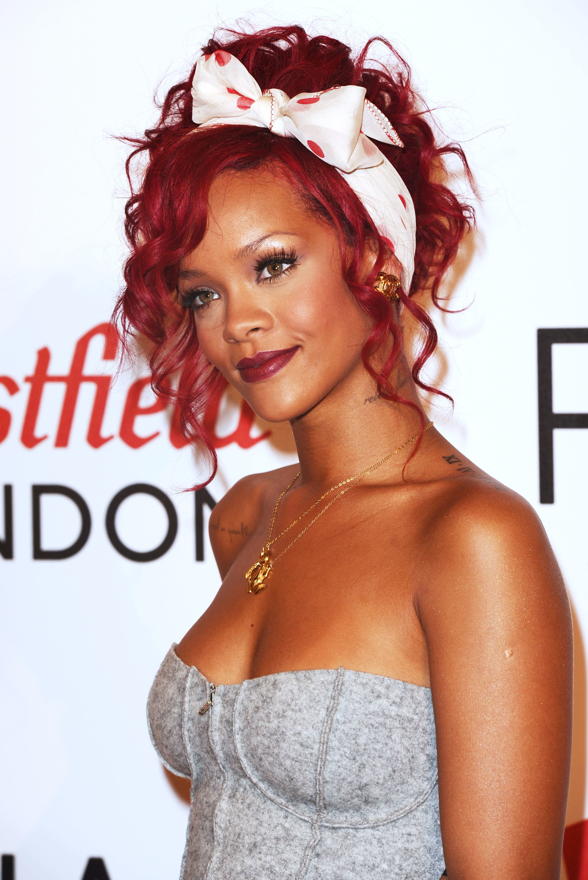 close up shot of rihanna with red curly hair tied up into a scarf updo at westfield shopping centre