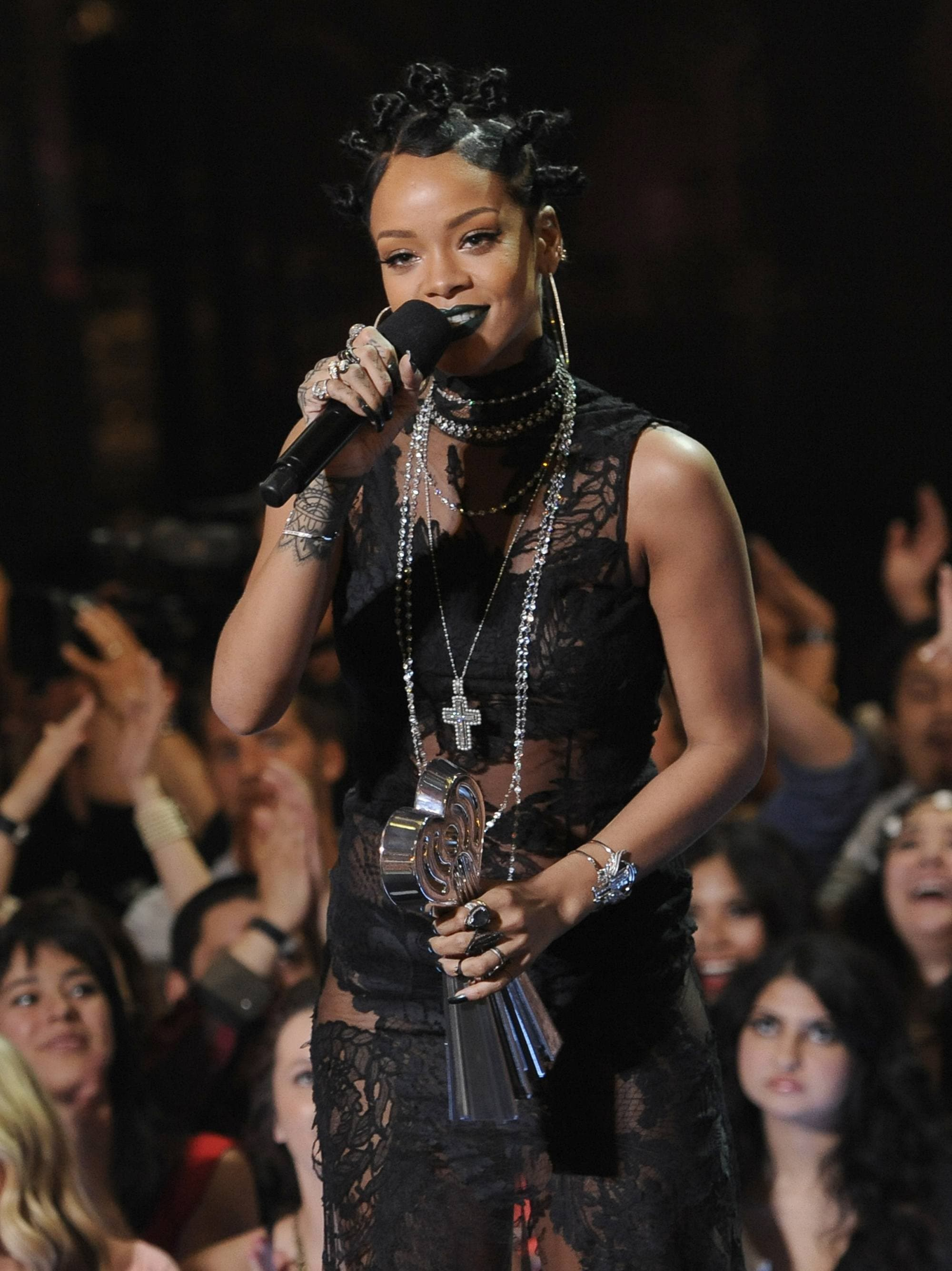 close up shot of rihanna at the iheartradio music awards with bantu knot hairstyle, wearing all black and holding award