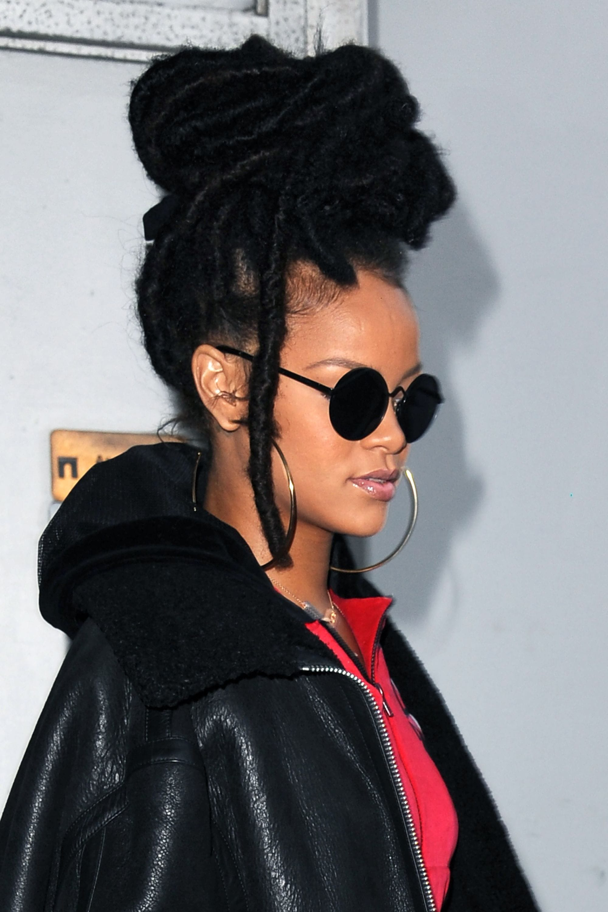 close up shot of rihanna with faux dreadlocks hairstyle, fashioned into a high bun updo, wearing black jacket and sunglasses