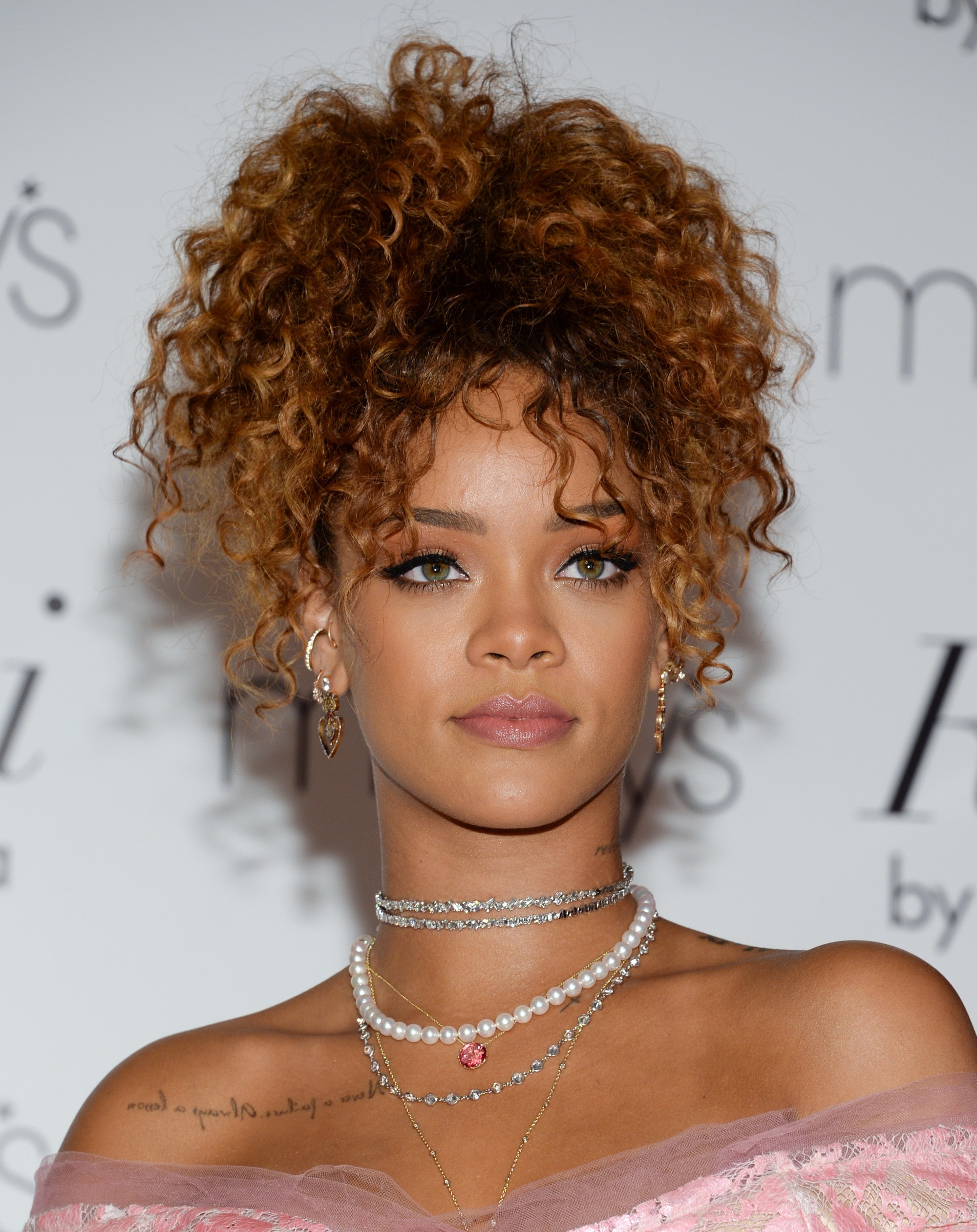 close up shot of rihanna at fragrance launch, wearing her hair in a high curly ponytail and pink dress
