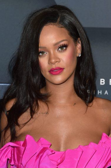 Rihanna with medium length rich natural brown dark hair, with pink lipstick and matching pink dress on the red carpet