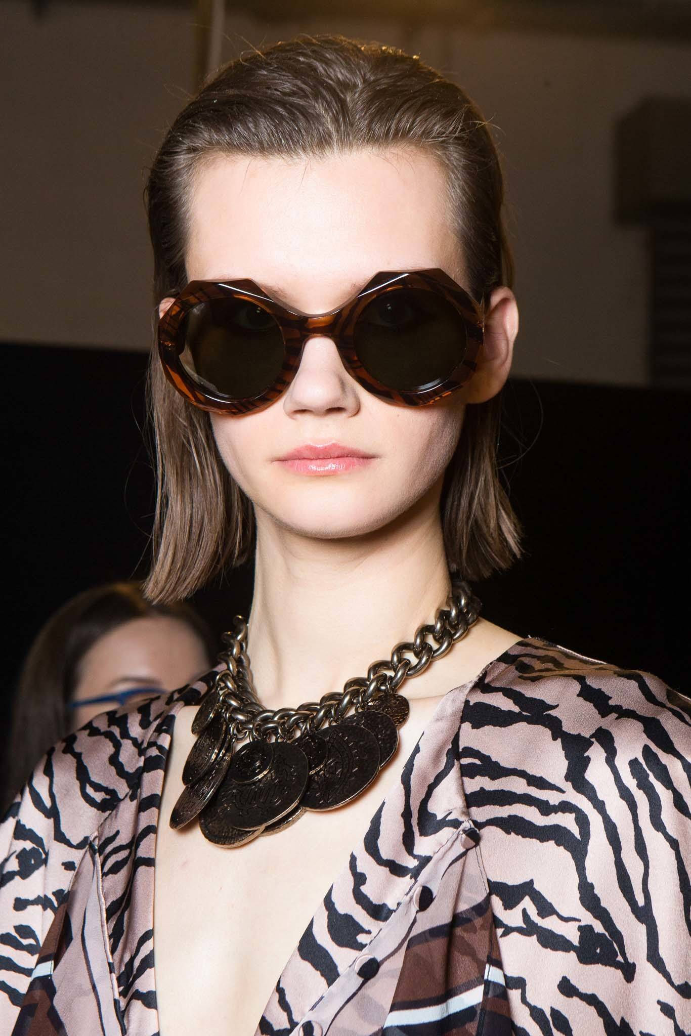 Christmas hairstyles: Model with short brown straight hair, styled swept back wearing large dark sunglasses and animal print top and large necklace at Roberto Cavalli FW18 show.