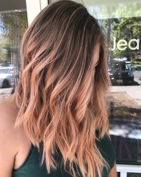 woman with an a wavy angled lob in a light pastel rose gold colour