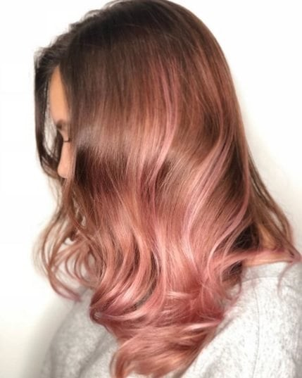 side profile of a woman with glossy rose gold hair