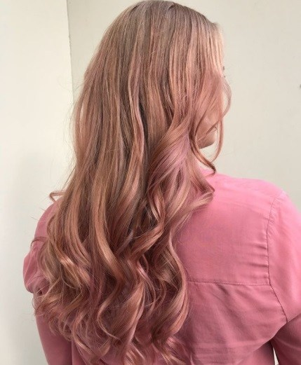 back view of a woman with long curly rose gold hair
