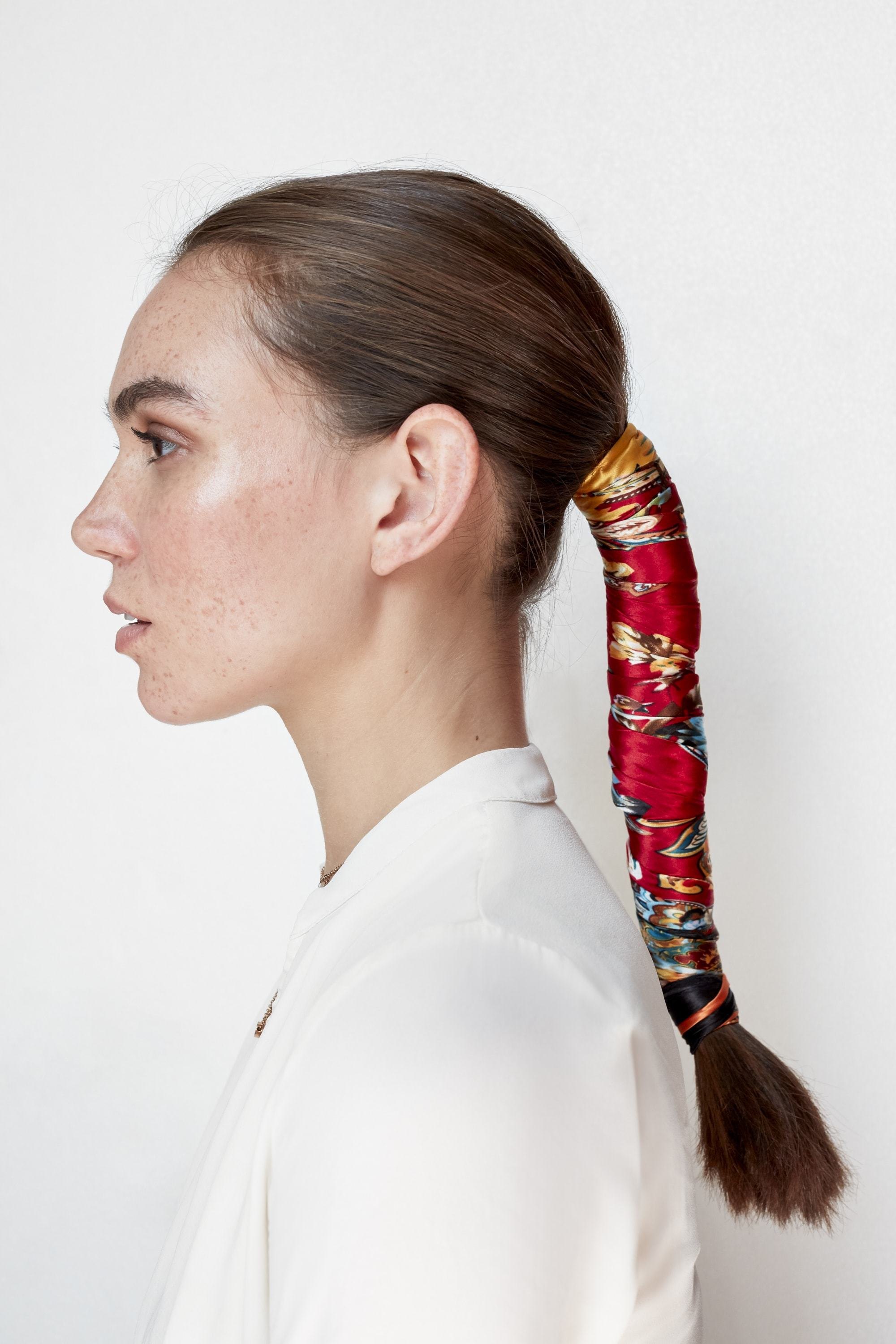 Christmas hairstyles: Brunette model with long straight hair in low ponytail, wrapped with a red headscarf wearing a white top.