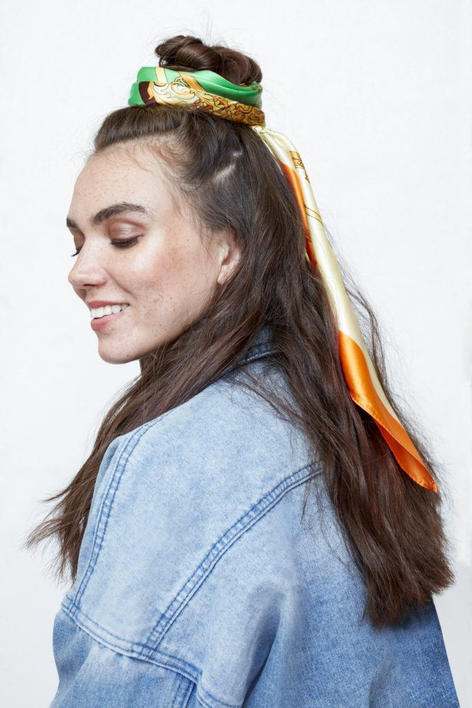 hair updos: brunette model with long brown hair in half-up, half-down bun with headscarf wrapped around the bun wearing denim jacket