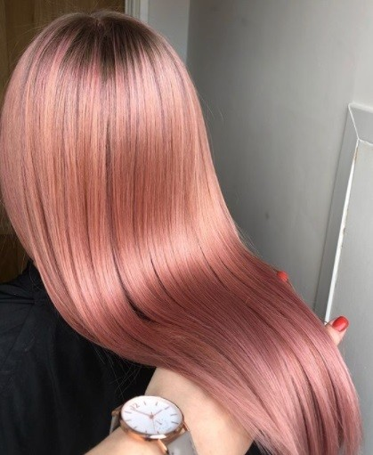 behind view of a woman with very long and shiny rose gold pink hair