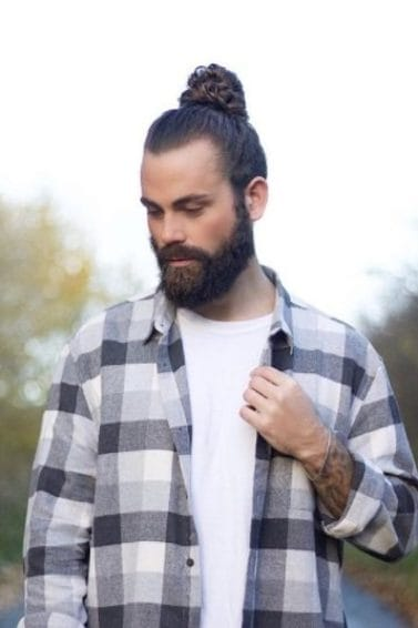 brunette man with a slicked back man bun and a beard