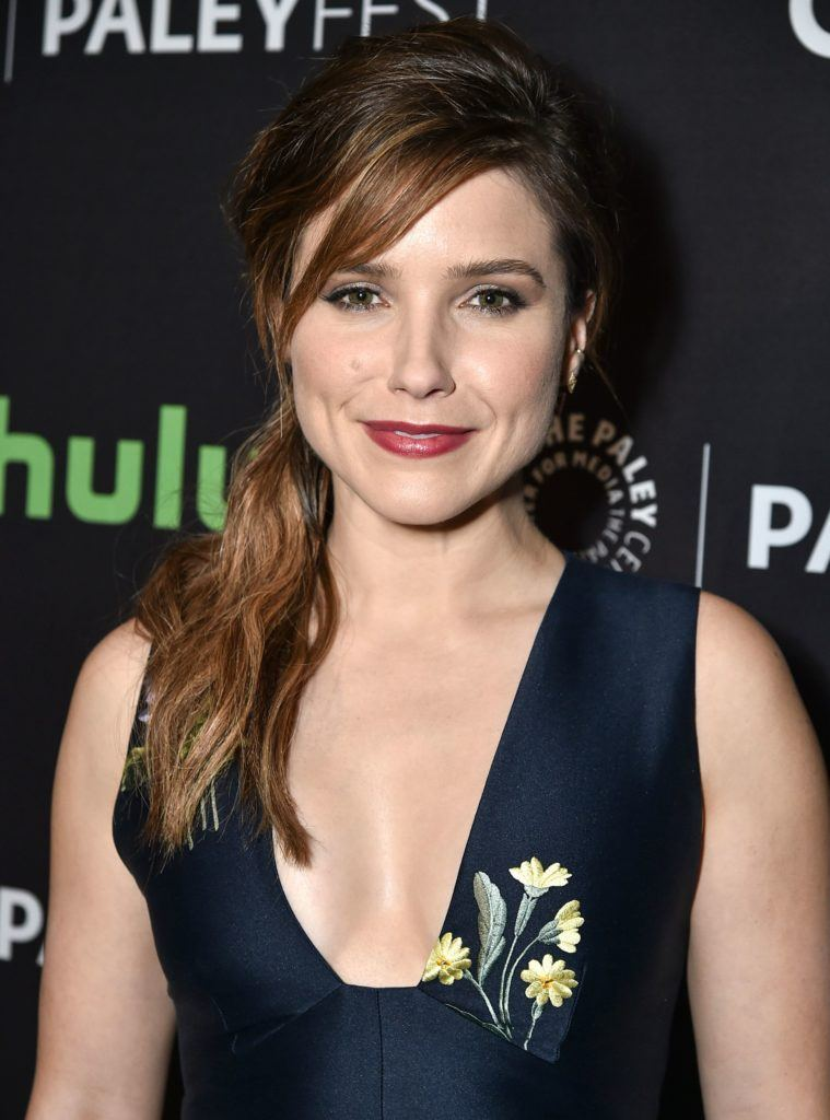 Ponytail with bangs: Sophia Bush with medium long reddish brown hair in side ponytail with side bangs