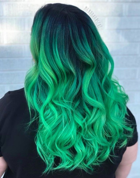 back view of a woman with long curly sour green apple coloured hair
