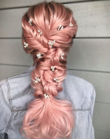 Fishtail braids: Woman with unicorn pink hair with several braids and flowers in her hair.