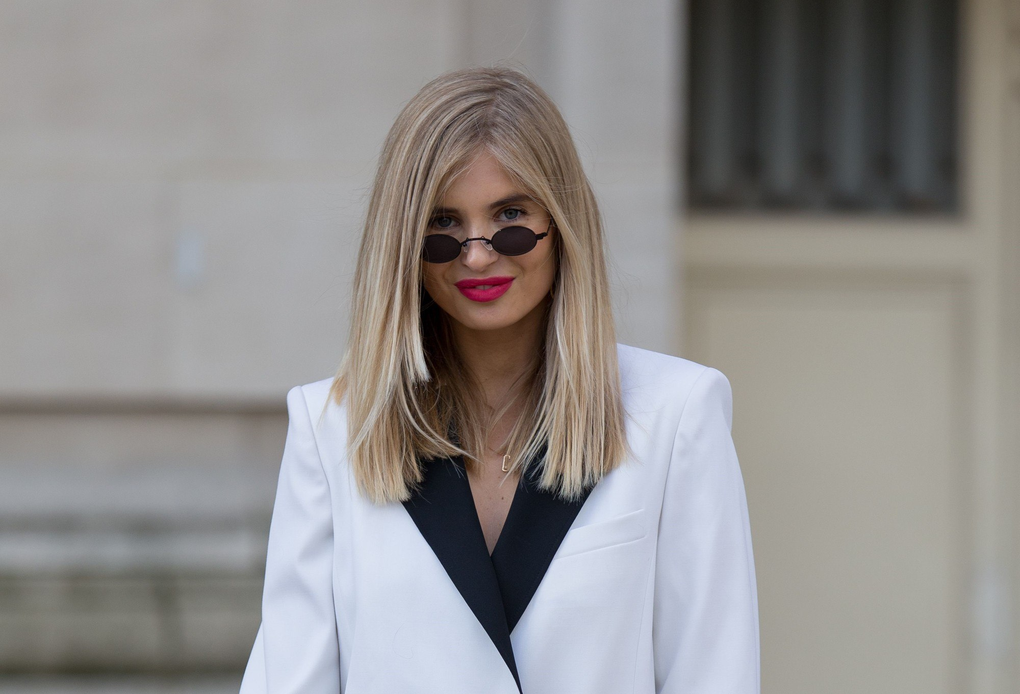 close up shot of a street style model with a natural blonde roots melted into a ashy blonde hair colour, wearing a white suit jacket and sunglasses, posing outside