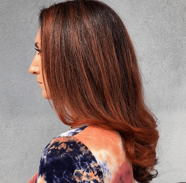 Cinnamon hair colour: Side shot of a woman with mid-length loosely waved hairstyle with cinnamon highlights in it.