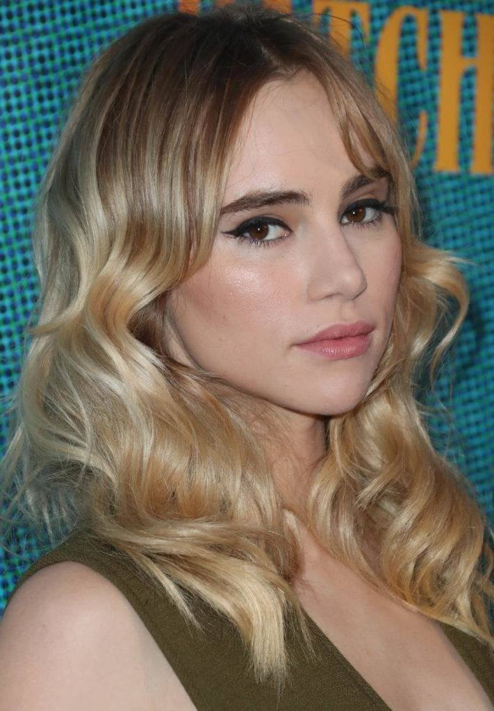 Shades of blonde hair: Suki Waterhouse with wavy blonde balayage medium length hair with long centre parted fringe.