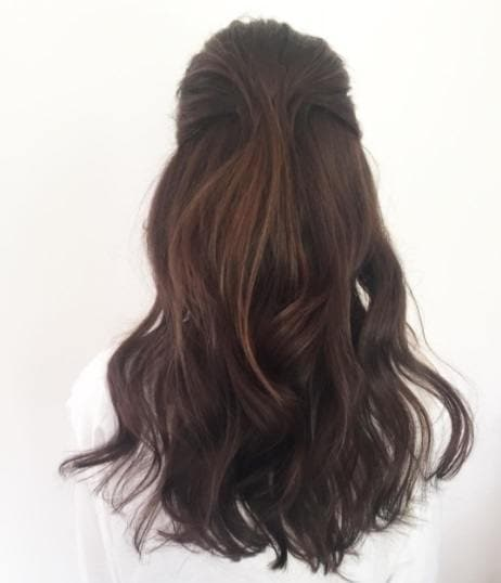 6 formal hairstyles for long hair to help you prep for party season back view of a woman with dark brown hair in a swept back half up do urmus Choice Image