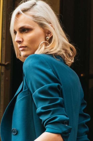Woman with volumised blonde medium-length hair, wearing teal blue suit jacket while posing outside a golden hotel