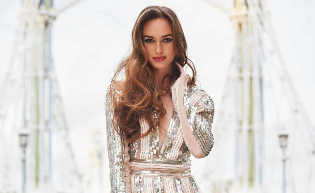Party hairstyles: Woman with brown highlighted long hair in bouncy waves wearing party sequin dress.